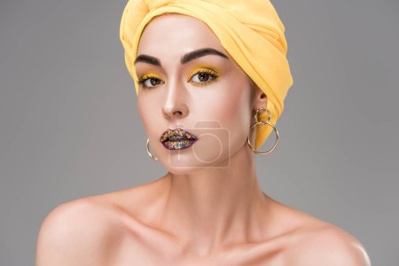 beautiful naked woman with stylish makeup wearing yellow head wrap and looking at camera isolated on grey
