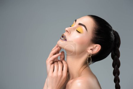 side view of sensual brunette girl with stylish makeup and closed eyes isolated on grey