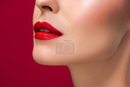 cropped shot of young woman with juicy red lips isolated on red