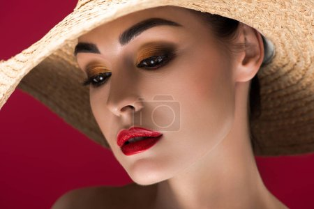 beautiful girl with stylish makeup wearing straw hat and looking down isolated on red