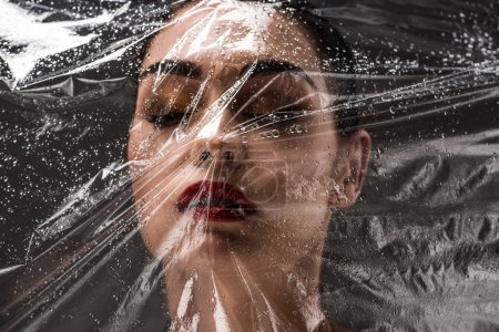 view through wet cellophane at beautiful young woman with closed eyes on black