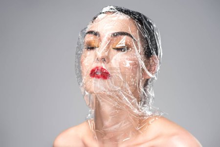 sensual young woman with transparent wet cellophane on head and closed eyes isolated on grey