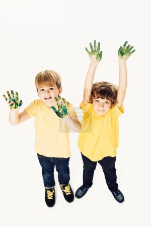 high angle view of happy little boys with hands in paint smiling at camera isolated on white