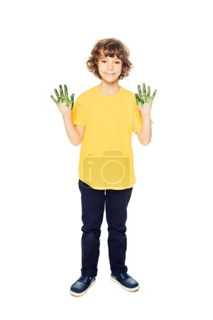 cute little boy showing hands in paint and smiling at camera isolated on white