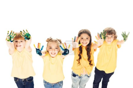 high angle view of adorable happy kids showing hands in paint and smiling at camera isolated on white