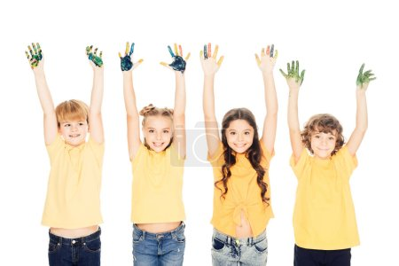 adorable happy kids showing hands in paint and smiling at camera isolated on white