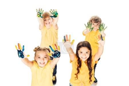 high angle view of happy children showing hands in paint and smiling at camera isolated on white