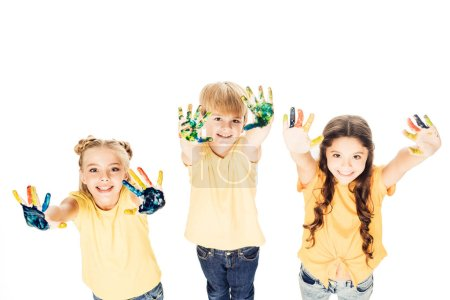 high angle view of happy kids showing hands in paint and smiling at camera isolated on white