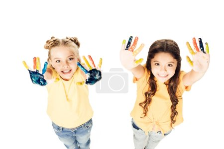 high angle view of adorable kids showing colorful painted hands and smiling at camera isolated on white