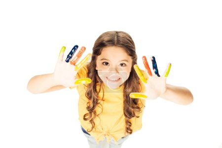 high angle view of adorable child showing colorful painted hands and smiling at camera isolated on white