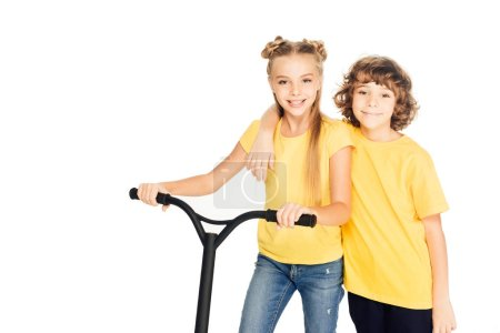 cute happy kids standing with scooter and smiling at camera isolated on white