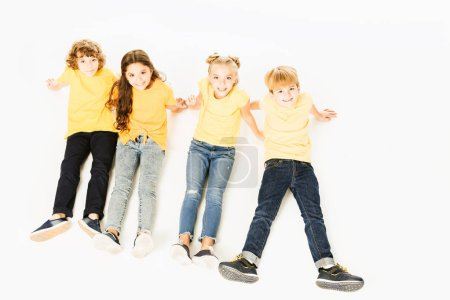 high angle view of adorable happy kids in yellow t-shirts sitting together and smiling at camera isolated on white