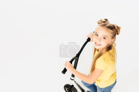 Foto de Vista de ángulo alto de adorable niño feliz montando motos y sonriendo a cámara aislada en blanco - Imagen libre de derechos