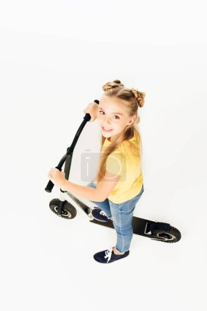 high angle view of beautiful happy child riding scooter and smiling at camera isolated on white
