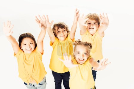high angle view of group of happy children showing hands and smiling at camera isolated on white