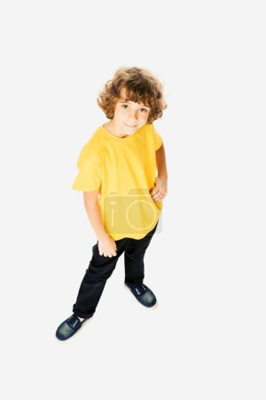 high angle view of cute little boy standing with hand on waist and smiling at camera isolated on white