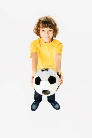 Photo for High angle view of adorable boy holding soccer ball and smiling at camera isolated on white - Royalty Free Image
