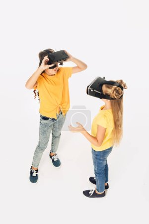 high angle view of beautiful kids using virtual reality headsets isolated on white