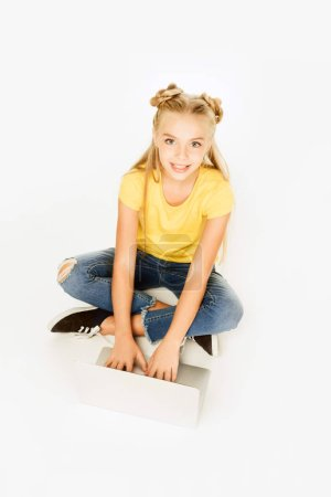 high angle view of beautiful happy kid using laptop and smiling at camera isolated on white