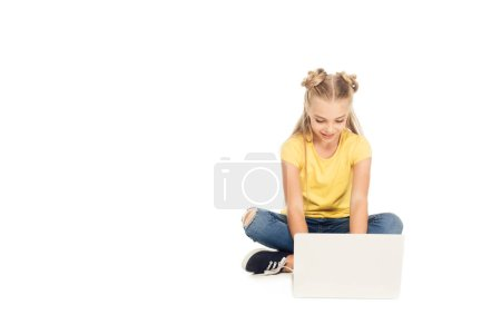 beautiful smiling child sitting and using laptop isolated on white