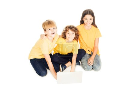 high angle view of adorable happy kids using laptop and smiling at camera isolated on white