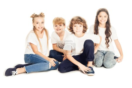 group of beautiful happy kids sitting together and smiling at camera isolated on white
