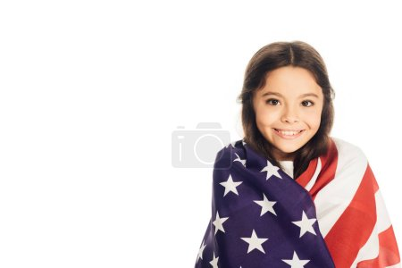 smiling adorable kid wrapped in american flag looking at camera isolated on white
