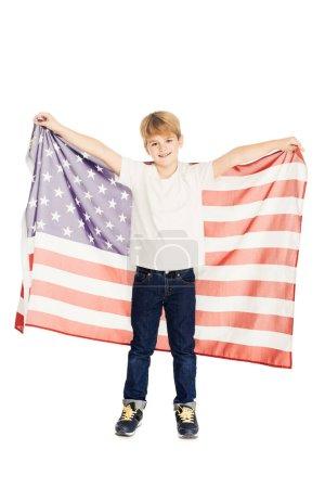 Foto de Adorable niño sosteniendo la bandera americana y mirando a cámara aislada en blanco sonriente - Imagen libre de derechos
