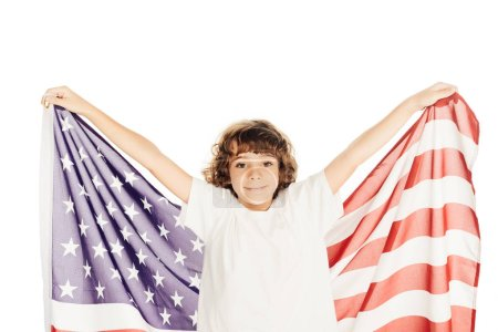 smiling adorable boy holding american flag and looking at camera isolated on white