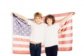 smiling adorable boys holding american flag and looking at camera isolated on white