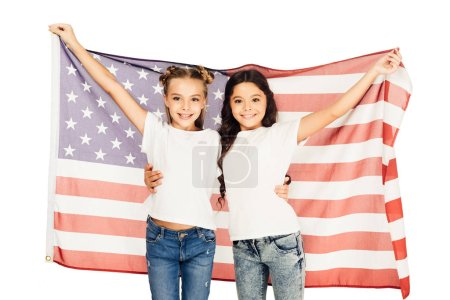cheerful adorable kids standing under american flag and looking at camera isolated on white