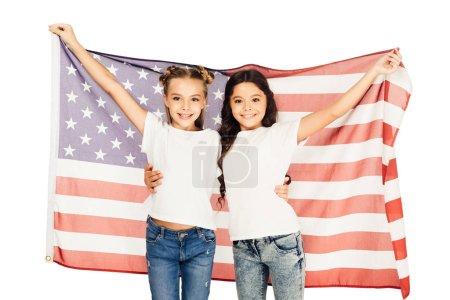 Photo pour Joyeux enfants adorables debout sous le drapeau américain et regardant la caméra isolé sur blanc - image libre de droit