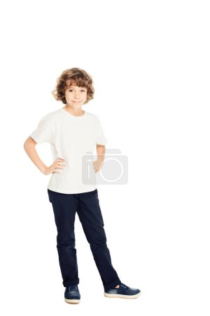 smiling adorable boy standing with hands akimbo and looking at camera isolated on white