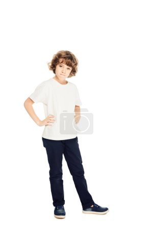 Photo for Irritated boy standing with hands akimbo and looking at camera isolated on white - Royalty Free Image