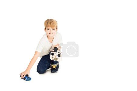 Foto de Adorable niño jugando con coches de radio controlada aislado sobre fondo blanco y mirando a cámara - Imagen libre de derechos