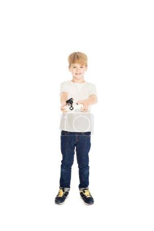 Photo pour Adorable garçon tenant télécommande isolé sur blanc et vous cherchez à la caméra - image libre de droit