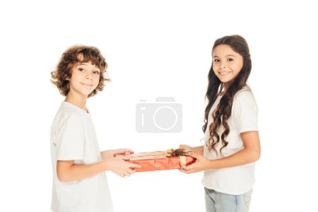 side view of cheerful boy presenting gift box to friend isolated on white and they looking at camera