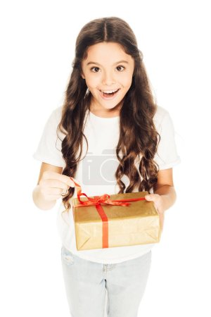 high angle view of excited adorable child holding gift box and looking at camera isolated on white