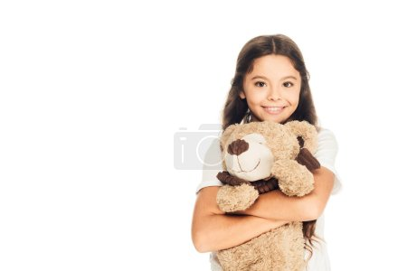 smiling adorable child hugging teddy bear isolated on white and looking at camera