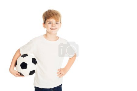 smiling adorable boy holding football ball and looking at camera isolated on white