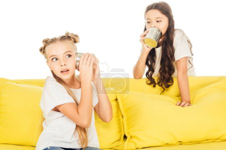 excited kids playing with tin cans phone on yellow sofa isolated on white