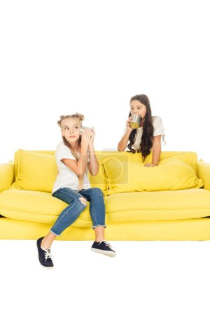 kids playing with tin cans phone on yellow sofa isolated on white