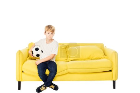 adorable boy sitting with football ball on yellow sofa isolated on white and looking at camera