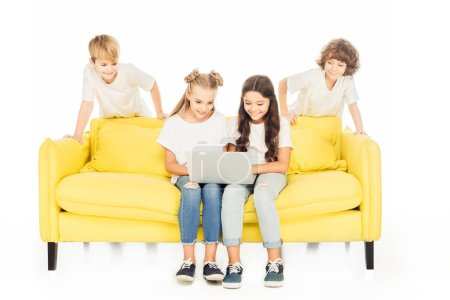 Photo for Children using laptop on yellow sofa isolated on white - Royalty Free Image