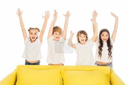 happy children standing behind yellow sofa with raised hands isolated on white
