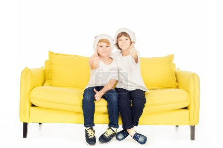 Photo for Adorable boys in santa hats sitting on yellow sofa isolated on white and showing thumbs up - Royalty Free Image