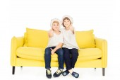 adorable boys in santa hats sitting on yellow sofa isolated on white and showing thumbs up