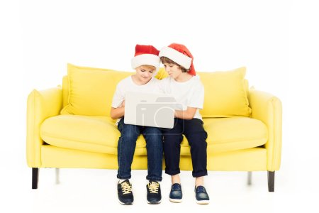 Photo for Adorable boys in santa hats sitting on yellow sofa and using laptop isolated on white - Royalty Free Image