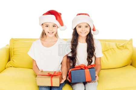 Photo for Smiling adorable kids in santa hats sitting on yellow sofa with presents isolated on white - Royalty Free Image