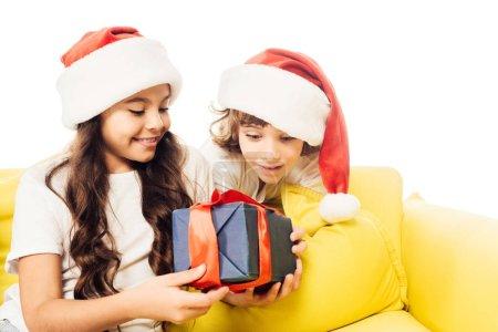 Foto de Emocionados los niños adorables con sombreros de santa mirando actualmente aislado en blanco - Imagen libre de derechos